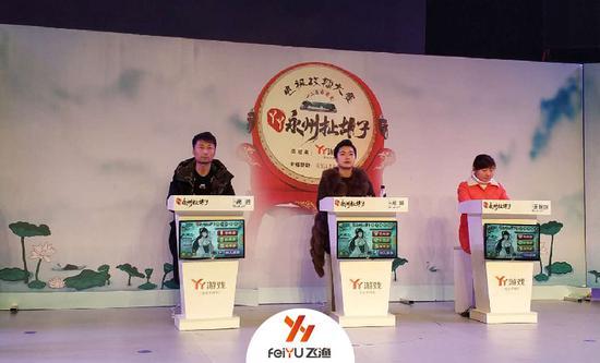 三位选手在台上比拼牌技