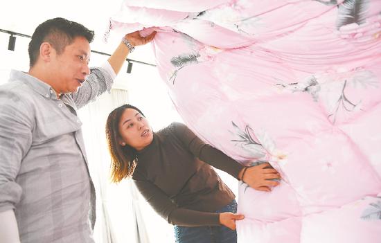 ▲ 11月12日,客商在选购固镇镇泓笙家纺加工制作的鹅绒被等羽绒制品。