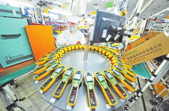 图为工人们加班加点生产红外测温仪。