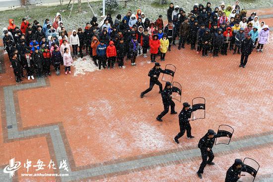 淮北市公安局相山公安分局巡防大队民警为学生表演警棍盾牌术。