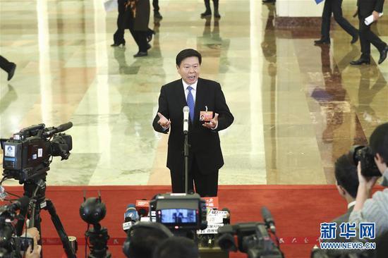 """3月12日,十三届全国人大二次会议在北京人民大会堂举行第三次全体会议。这是国家税务总局局长王军在""""部长通道""""接受采访。 新华社记者殷刚摄"""