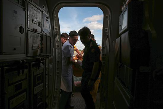 8月23日,在老挝万象,中老两军医护人员将受伤的中国游客送上飞机。在老挝北部遭遇车祸受伤的20名中国游客23日下午从老挝首都万象瓦岱国际机场乘机回国。新华社 图