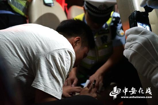 被查到饮酒驾驶的司机正在处罚单上签字