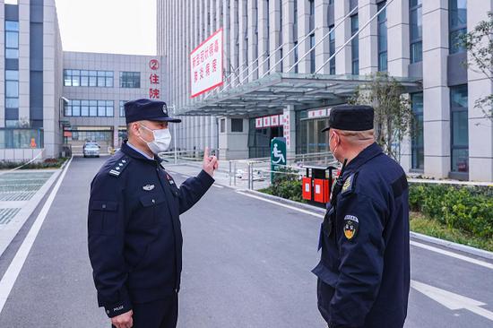 亳州市公安局治安支队四大队民警在新冠肺炎患者定点收容医院,为保安员讲解防护知识。