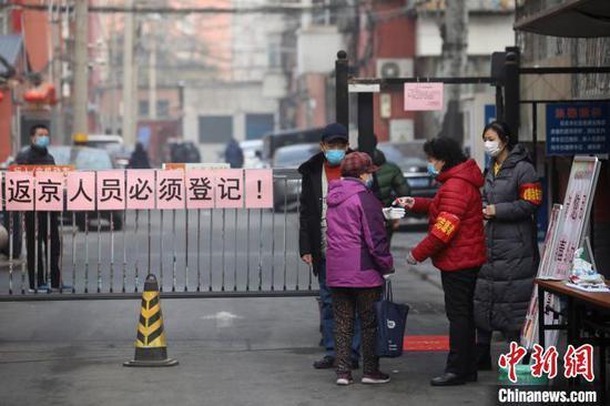 资料图:北京丰台北大地西区社区大门口设立了排查点,三、两个带着红袖箍的党员干部正在值守,并对出入人员测温。 中新社记者 盛佳鹏 摄