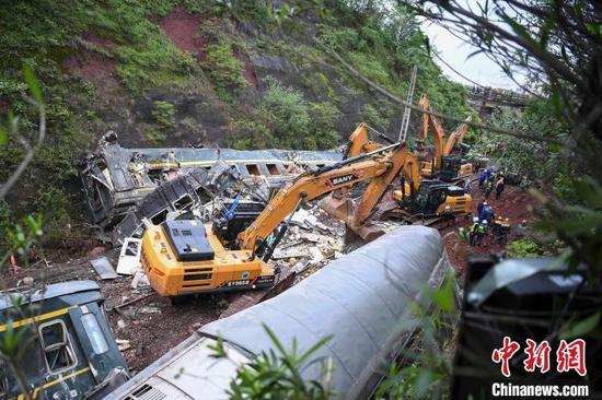 事故现场,数台挖掘机、轨道车等加快抢修救援。 杨华峰 摄
