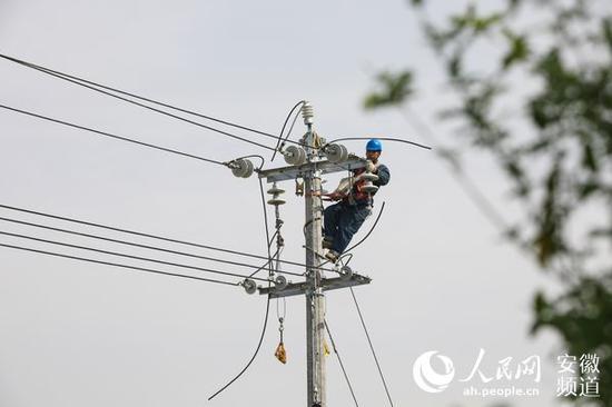 电力施工人员在霍山县上土市镇上土市村进行放紧线施工。张俊 摄