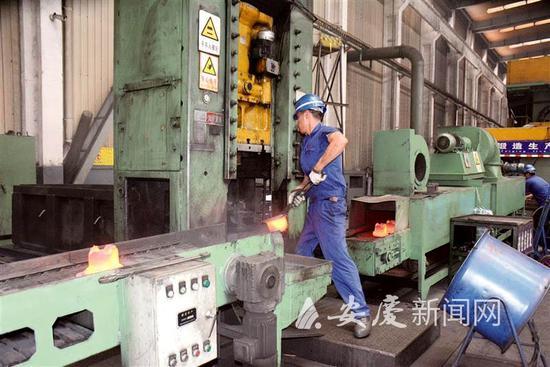 8月12日,工人正在用火钳搬运高达1200度的钢制活塞。 记者 路欣 摄