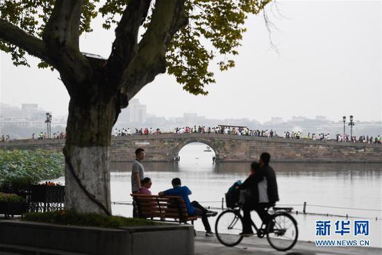 10月7日,游客在杭州西湖风景区休闲游玩。新华社记者 黄宗治 摄