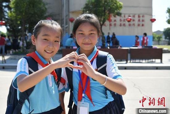 """9月7日,在安徽省庐江县同大镇中心小学,孩子们背着""""爱心书包""""做心造型。韩苏原 摄"""