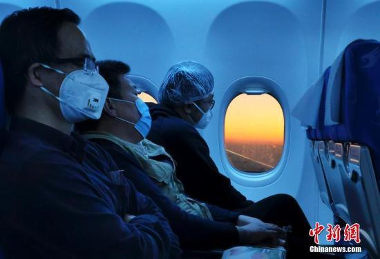 资料图:飞机上乘客佩戴口罩出行。中新社记者 杜洋 摄