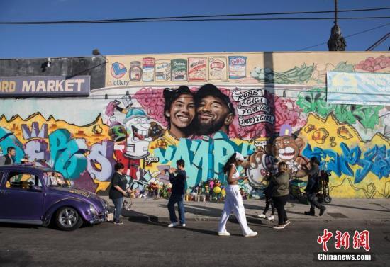 当地时间1月28日,球迷们来到洛杉矶一处绘有科比·布莱恩特及其二女儿吉安娜的壁画前寄托哀思。中新社记者 刘关关 摄