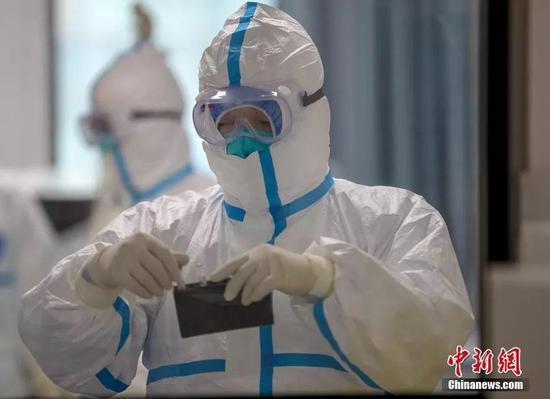 资料图:武汉市疾控中心检测组工作人员进行病毒检测。中新社记者 张畅 摄