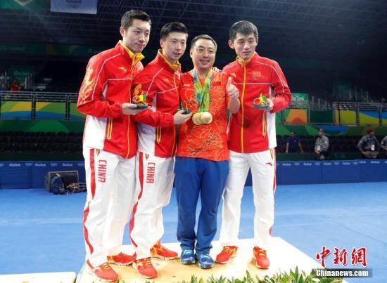 当地时间8月17日,2016里约奥运男子乒乓球团体赛决赛举行,中国队最终以总比分3:1的成绩战胜日本队获得冠军。许昕(左一)、马龙(左二)、刘国梁(右二)、张继科在领奖台上合影。中新网记者 盛佳鹏 摄