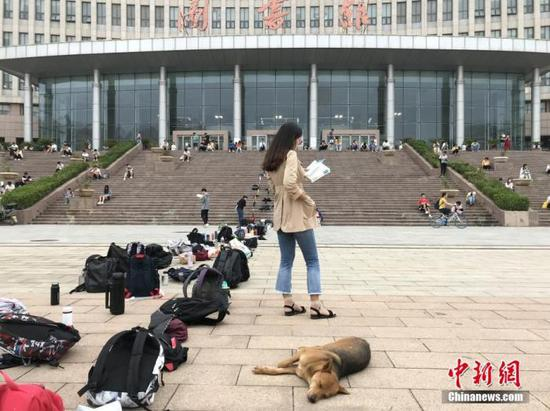 不少考生为抢占图书馆作为,用书包等站队。图为一名大学生在图书馆门前排队、背书。 韩章云 摄