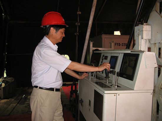 朱恒银同志在现场调试自行研制的具有国际先进水平的钻机操作系统