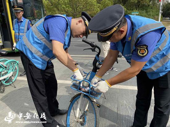 城管队员以共享单车运维人员的身份,对路边的共享单车进行整理