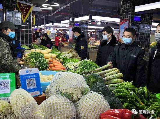 图为胡勇芳(右二)在检查蔬菜价格