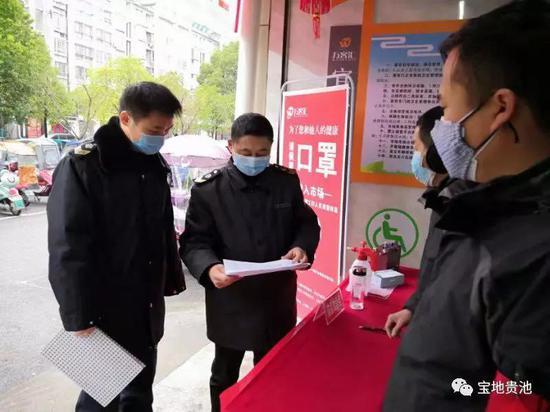图为胡勇芳(左二)在农贸市场防控点检查