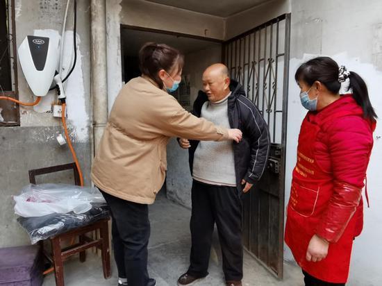 图为社区工作人员给孤寡老人送御寒衣物