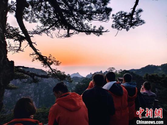 游客在黄山之巅看日出。 叶若愚 摄