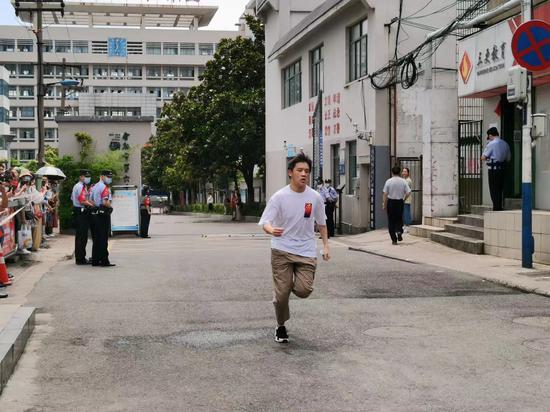 在合肥六中南区考点,伴随着考试结束的铃声,一个考生奔跑出考场,两边的家长为他鼓掌呐喊加油。