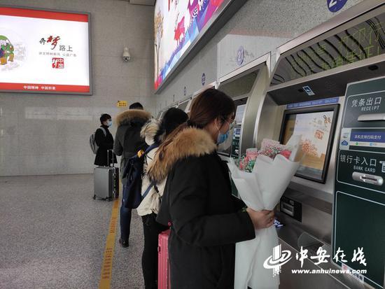 旅客在黄山北站自动售取票机前取票。(陆杨摄)