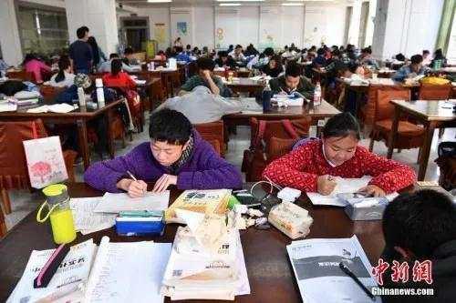 资料图:昆明中小学生在图书馆自习室内写作业。
