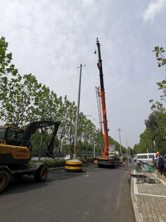 图为工人正在拔除天水路上的高压杆线