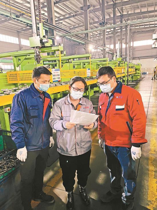 图为粤美金属制品科技实业有限公司员工传看留厂过年优惠政策。