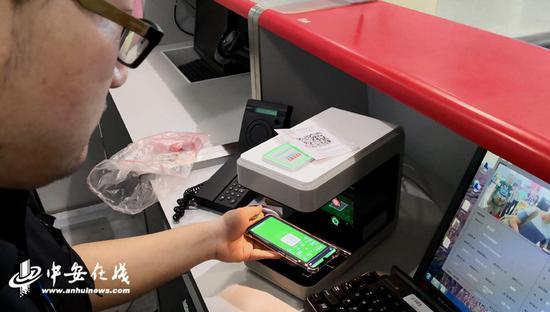 机场安检通过设备扫描旅客手机二维码完成验证流程。