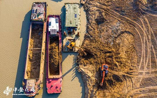 庐江县庐城镇境内的罗埠河水毁工程修复施工现场,大型机械在船只的配合下紧张施工