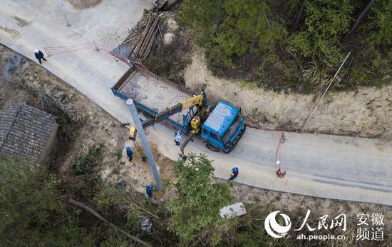电力施工人员在岳西县中关镇京竹村进行电杆组立施工。张俊 摄
