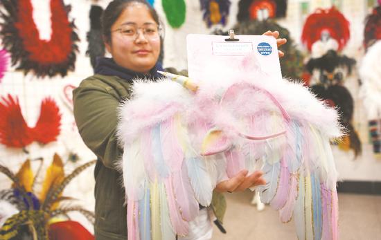 ▲ 11月12日,固镇镇一家公司职员在展示出口海外的鹅毛工艺品。