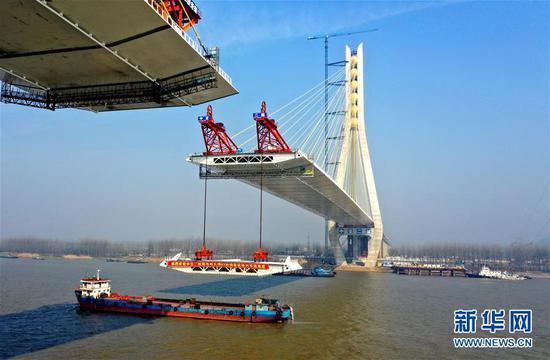 3月13日,在安徽池州长江公路大桥建设现场,中交二航局施工机械在吊装钢箱梁(无人机拍摄)