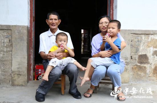 都老汉和儿媳妇坐在自家门前抱着两个孙子
