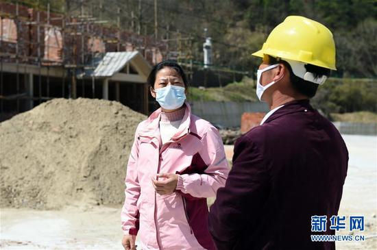 3月20日,在金寨县大湾村在建的漂流中转站,余静(左)与施工人员沟通复工复产有关事项。
