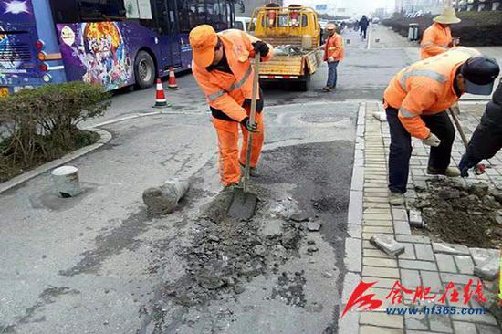 市政工人修补金寨路非机动车道的坑洞