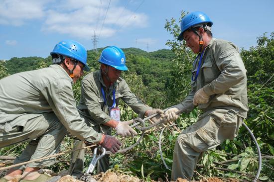 电力施工人员正在拆除塌陷山坡上电力线路