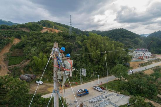 电力施工人员在新组立的电杆上架设35千伏电力线路