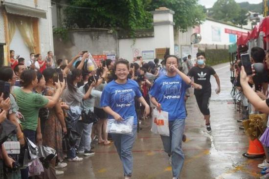 图为歙县中学考场外,考生结束考试笑着跑出考场。