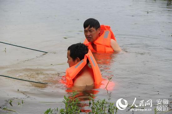 7月16日,陶有金(右)跳入水中查找圩堤渗漏情况。