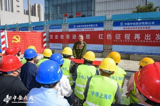 今年84岁的杨克美老人正在给现场施工人员讲述党的光辉历程