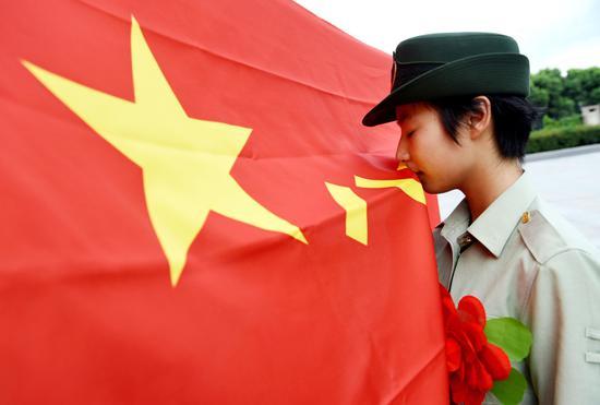 2018-11-15,安徽合肥,在武警合肥支队四中队退伍老兵告别警徽仪式上,一名退伍女兵亲吻武警部队旗。