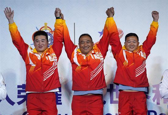 10月21日,中国队选手夏伟(中)、于小凯(左)、郭雨浩在颁奖仪式上。 当日,在武汉进行的第七届世界军人运动会男子飞碟多向团体赛中,中国队夺得冠军。 新华社记者万象 摄