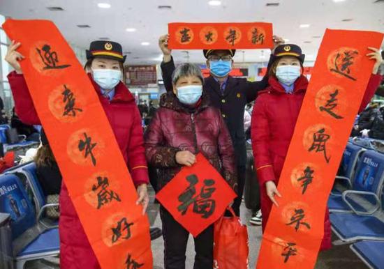 宿州站志愿者在为旅客送春联。