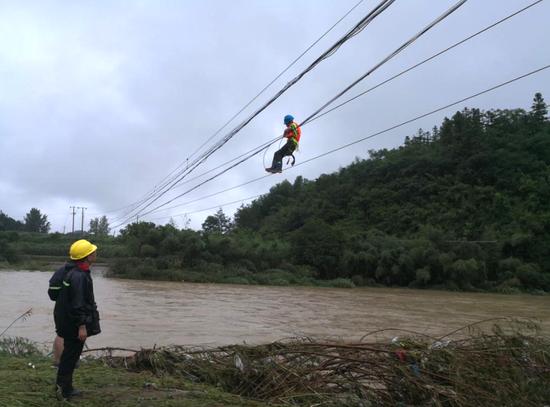 图为工作人员正在抢修绩溪至黄山省干光缆,身下就是湍急的洪水。