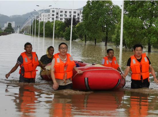 图为工作人员使用皮划艇运送抢修设备。
