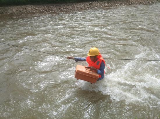 图为广德市移动工作人员在齐腰深的洪水中抢修光缆。