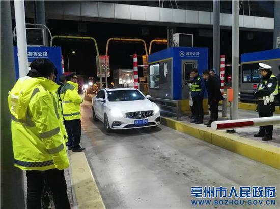 工作人员在亳州南收费站疏导车辆,并进行ETC相关政策宣传